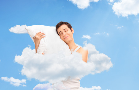 Joyful man sleeping and hugging a soft pillow up in clouds in the sky