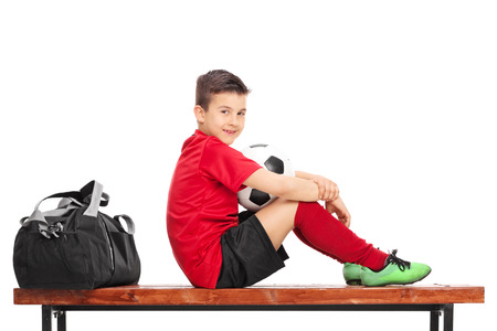 player bench: Junior football player in a red jersey holding a ball and sitting on a wooden bench isolated on white background