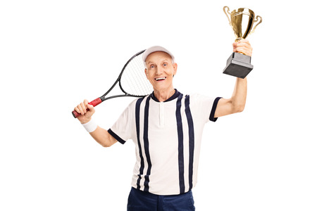 70s tennis: Senior amateur tennis player holding a golden trophy and smiling isolated on white background Stock Photo