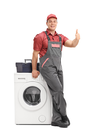 jumpsuit: Full length portrait of a male repairman leaning on a washing machine and giving a thumb up isolated on white background