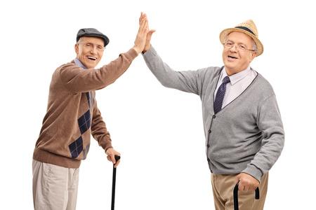 Twee vrolijke senior heren high-five elkaar en kijken naar de camera op een witte achtergrond