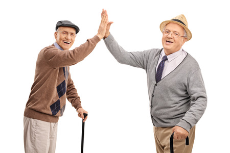 old sign: Two cheerful senior gentlemen high-five each other and looking at the camera isolated on white background