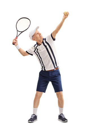 70s tennis: Full length profile shot of a senior tennis player preparing to serve isolated on white background