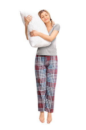 midair: Full length portrait of a calm woman hugging a pillow and sleeping shot in mid-air isolated on white background Stock Photo