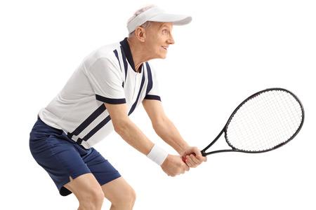 hombre con sombrero: Perfil de disparo de un hombre mayor jugando al tenis activo aislado sobre fondo blanco