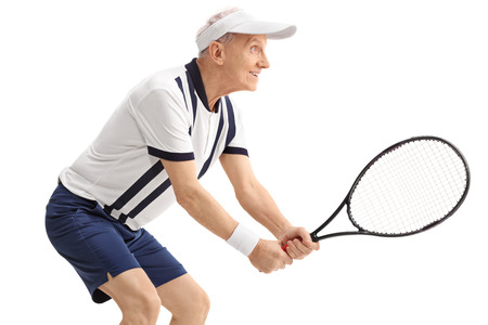 70s tennis: Profile shot of an active senior man playing tennis isolated on white background Stock Photo