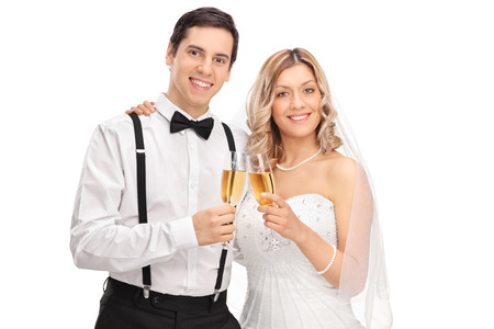 happy wedding: Studio shot of a newlywed couple holding glasses of white wine and posing together isolated on white background