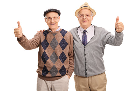 posing  agree: Two senior friends posing together and giving a thumb up isolated on white background Stock Photo