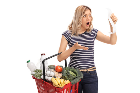 disbelief: Shocked woman holding a shopping basket full of groceries and looking at the bill in disbelief isolated on white background