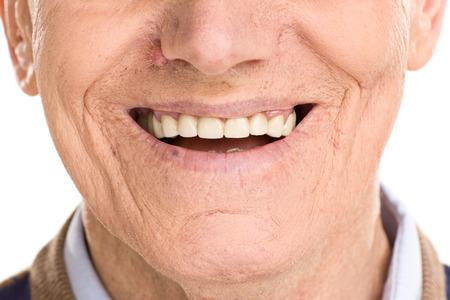 白い背景に分離されて笑っている陽気な年配の男性にクローズ アップ