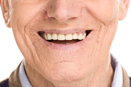 Close-up on cheerful senior man smiling isolated on white background