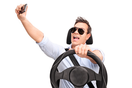 reckless: Young man driving and taking a selfie with his cell phone isolated on white background Stock Photo
