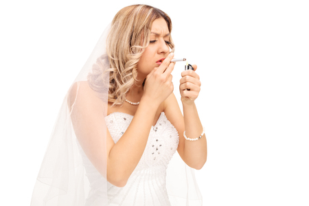 freaked out: Young nervous bride lighting up a cigarette isolated on white background Stock Photo