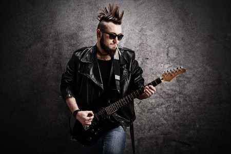 rocker: Young punk rocker playing electric guitar and leaning against a concrete wall