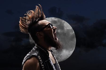 Junger Mann mit einem Irokesenschnitt vor einem Vollmond in der Nacht schreit