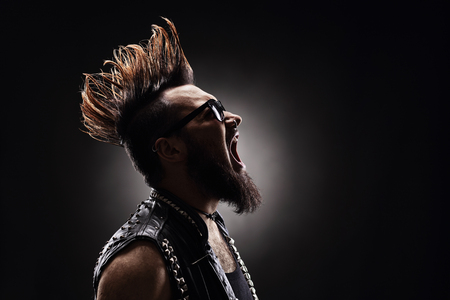 man shouting: Profile shot of an angry punk rocker shouting on dark background Stock Photo