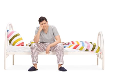 Triste giovane seduto su un letto e contemplare isolato su sfondo bianco
