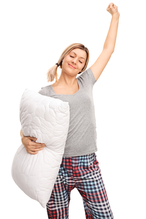 woman stretching: Vertical shot of a young woman in pajamas holding a pillow and stretching herself isolated on white background
