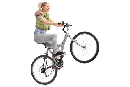 wheelie: Young woman doing a wheelie on a bicycle isolated on white background