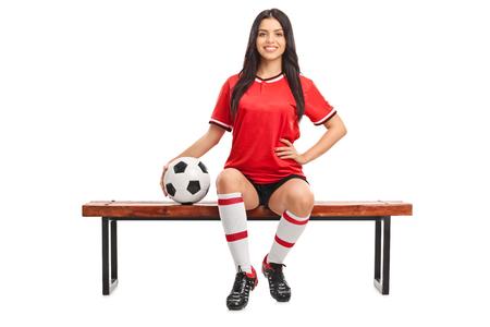 Junge weibliche Fußballspieler auf einer Holzbank sitzt und einen Ball auf weißem Hintergrund isoliert