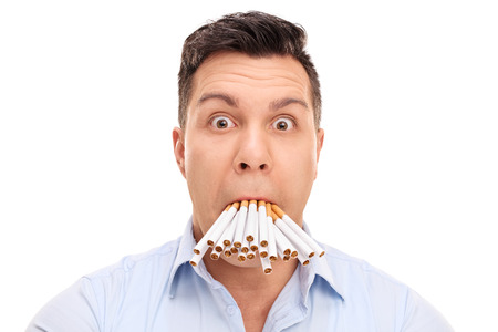 baffled: Baffled young man with a bunch of cigarettes in his mouth isolated on white background Stock Photo