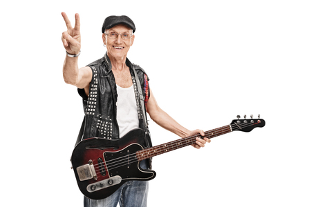 bass player: Senior punk bass player holding a guitar and making a peace hand gesture isolated on white background