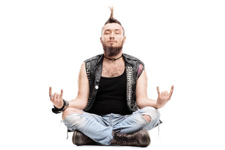 hombres jovenes: var�n punk meditando sentado en el suelo y haciendo un gesto de rock con las manos aisladas en el fondo blanco