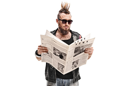 delinquent: Male punk rocker reading a newspaper isolated on white background