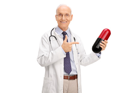 Mature doctor holding a huge pill and pointing towards it with his finger isolated on white background