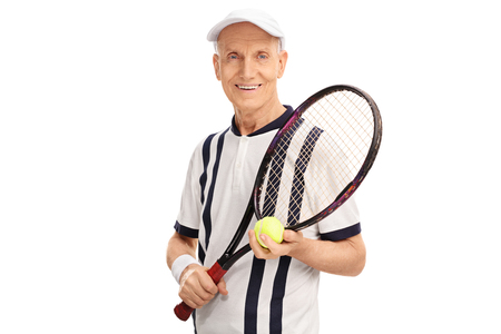 70s tennis: Studio shot of an amateur senior tennis player holding a racket and a ball isolated on white background Stock Photo