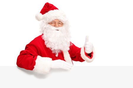 posing  agree: Santa Claus posing behind a white signboard and giving a thumb up isolated on white background