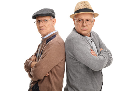 unbearable: Two seniors angry with each other standing back to back isolated on white background