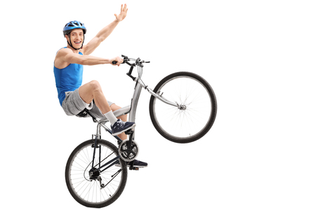 wheelie: Confident young biker performing a wheelie and holding the bike with one hand isolated on white background