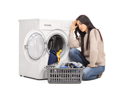 launder: Sad woman emptying a washing machine seated on the floor isolated on white background