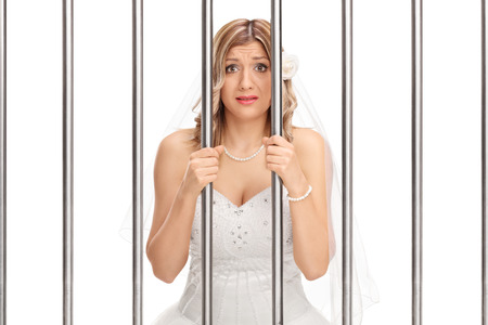 jail: Worried young bride standing behind bars in jail isolated on white background