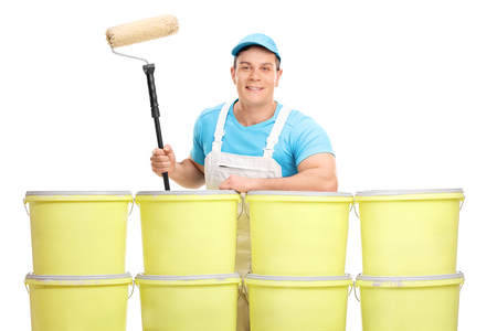 white color worker: Young male decorator posing behind a stack of color buckets isolated on white background