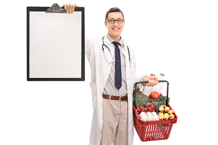 paper basket: Young doctor holding a shopping basket full of groceries and a clipboard isolated on white background Stock Photo