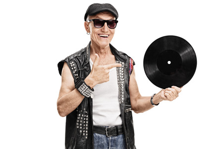 punk: Senior punk rocker holding a vinyl and pointing to it with his finger isolated on white background