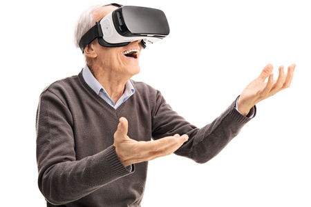visualizing: Amazed senior gentleman using a VR headset and gesturing with his hands isolated on white background