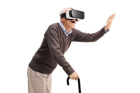 gentleman: Senior gentleman with a cane having fun using a VR headset isolated on white background Stock Photo