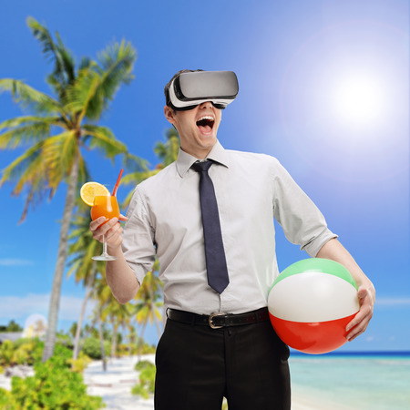 visualizing: Young businessman visualizing a beach environment using a VR headset and holding a cocktail and a beach ball shot with tilt and shift lens Stock Photo