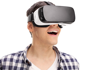 VIRTUAL REALITY: Young man experiencing virtual reality through a VR headset isolated on white background Stock Photo