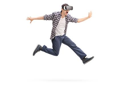 Aufgeregter junger Mann virtuelle Realität durch einen VR-Headset Schuss mitten in der Luft auf weißem Hintergrund zu erleben Standard-Bild