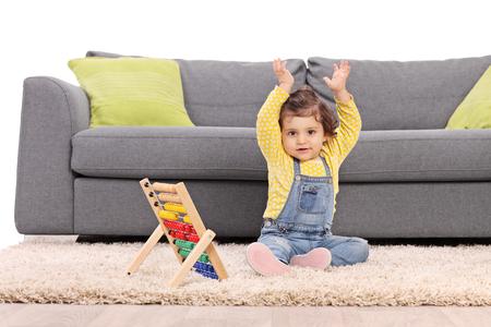 Bébé fille assise sur le sol en face d'un canapé gris et des gestes avec ses mains avec un boulier à côté d'elle isolé sur fond blanc Banque d'images