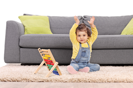 baby in hands: Baby girl sitting on floor in front of a gray sofa and gesturing with her hands with an abacus next to her isolated on white background