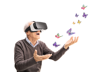 Joyful senior gentleman visualizing butterflies via VR headset isolated on white background