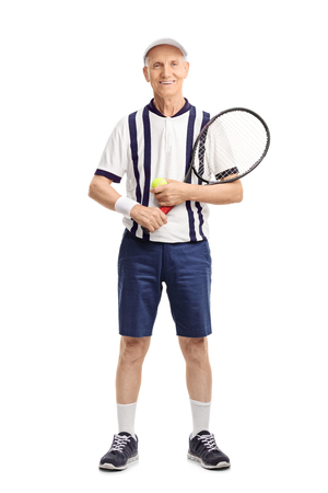 70s tennis: Full length portrait of a senior man holding a tennis racket and a ball isolated on white background