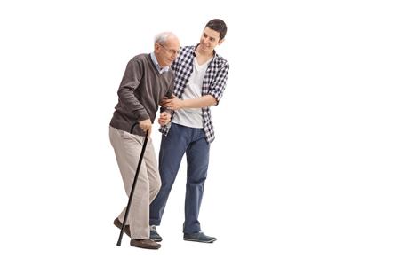 abuelos: hombre joven que ayuda a un señor mayor con un bastón aislado en el fondo blanco Foto de archivo