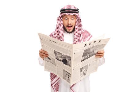 Sorprendido joven árabe que lee un periódico y que hace una expresión desconcertada aislado en el fondo blanco