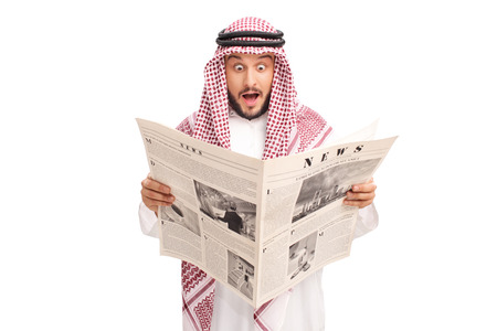 baffled: Surprised young Arab reading a newspaper and making a baffled expression isolated on white background
